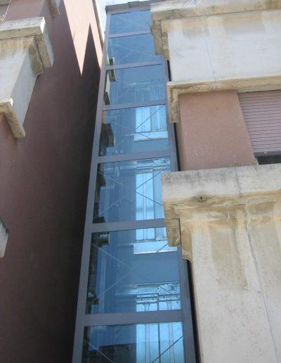 ascensore idraulico con incastellatura in lamiera di ferro verniciata da esterno tra palazzi