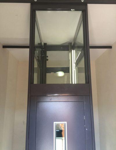 Ancoraggio al soffitto di ascensore con struttura in lamiera di acciaio autoportante tamponata con vetro trasparente