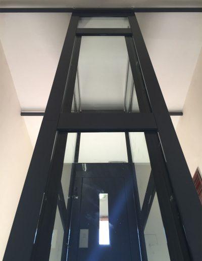 Vista da esterno retro di ascensore con struttura in lamiera di acciaio autoportante tamponata con vetro trasparente