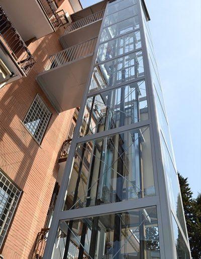 esterno piattaforma elevatrice idraulica con incastellatura in ferro verniciato portante da esterno con porte automatiche e passerelle di sbarco