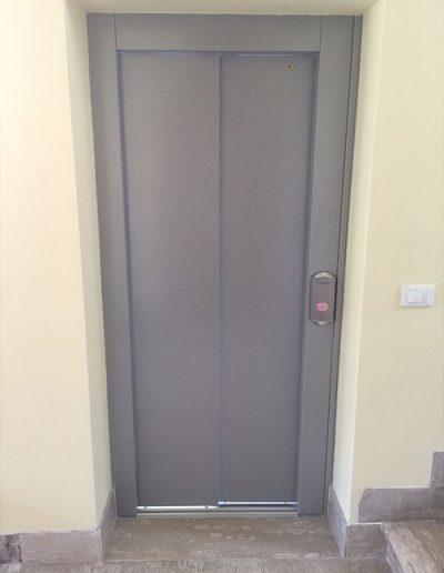 piattaforma elevatrice idraulica con incastellatura in ferro verniciato portante da esterno con porte automatiche porta interna