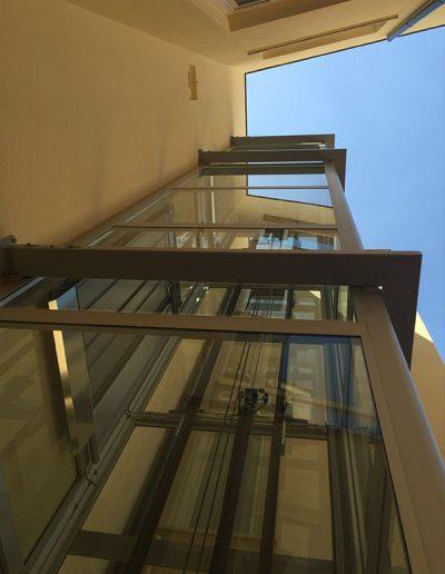 piattaforma elevatrice idraulica con incastellatura in ferro verniciato portante da esterno con porte automatiche per scuola comunale vista dal basso