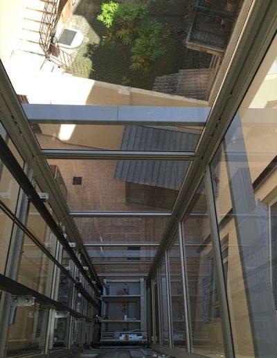 piattaforma elevatrice idraulica con incastellatura in ferro verniciato portante da esterno con porte automatiche per scuola comunale vista vano in vetro
