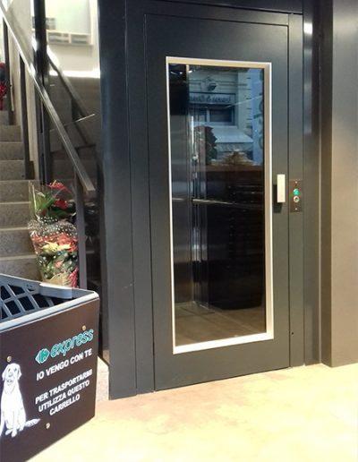piattaforma elevatrice con castello in vetro trasparente per pubblico esercizio vista porta piano inferiore