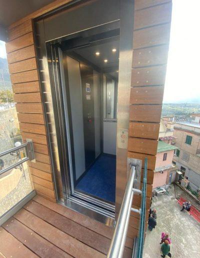Piattaforma elevatrice con vano rivestito in legno e porte automatiche accesso al piano