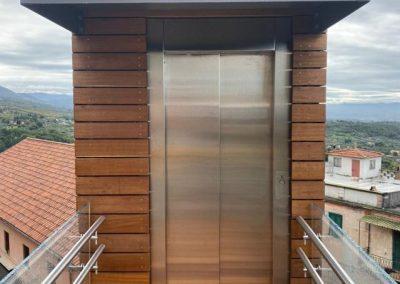 Piattaforma elevatrice con vano rivestito in legno e porte automatiche accesso frontale