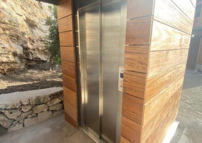 Piattaforma elevatrice con vano rivestito in legno e porte automatiche accesso inferiore