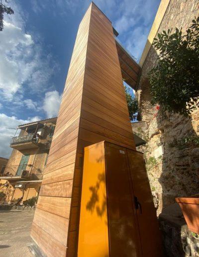 Piattaforma elevatrice con vano rivestito in legno e porte automatiche armadio comandi