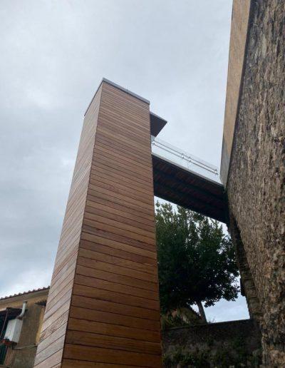 Piattaforma elevatrice con vano rivestito in legno e porte automatiche da terra