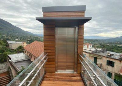 Piattaforma elevatrice con vano rivestito in legno e porte automatiche rampa di accesso