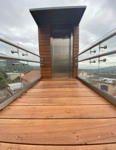 Piattaforma elevatrice con vano rivestito in legno e porte automatiche rampa superiore